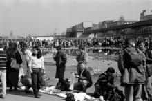 Käufer und Verkäufer auf dem Polenmarkt in Berlin. Im Hintergrund die Haltestelle der damals im Testbetrieb befindlichen Magnetbahn.