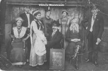 Laientheatergruppe mit Tafel (Inschrift: Z Teatru Polskiego z Husen dnia 23.3. roku 1919), markiert: Viktoria Wasielewski